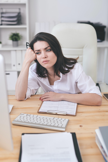 Woman sitting at desk not knowing what to do next