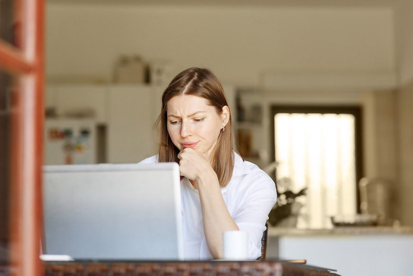 Frustrated woman staring at her laptop trying to write a book